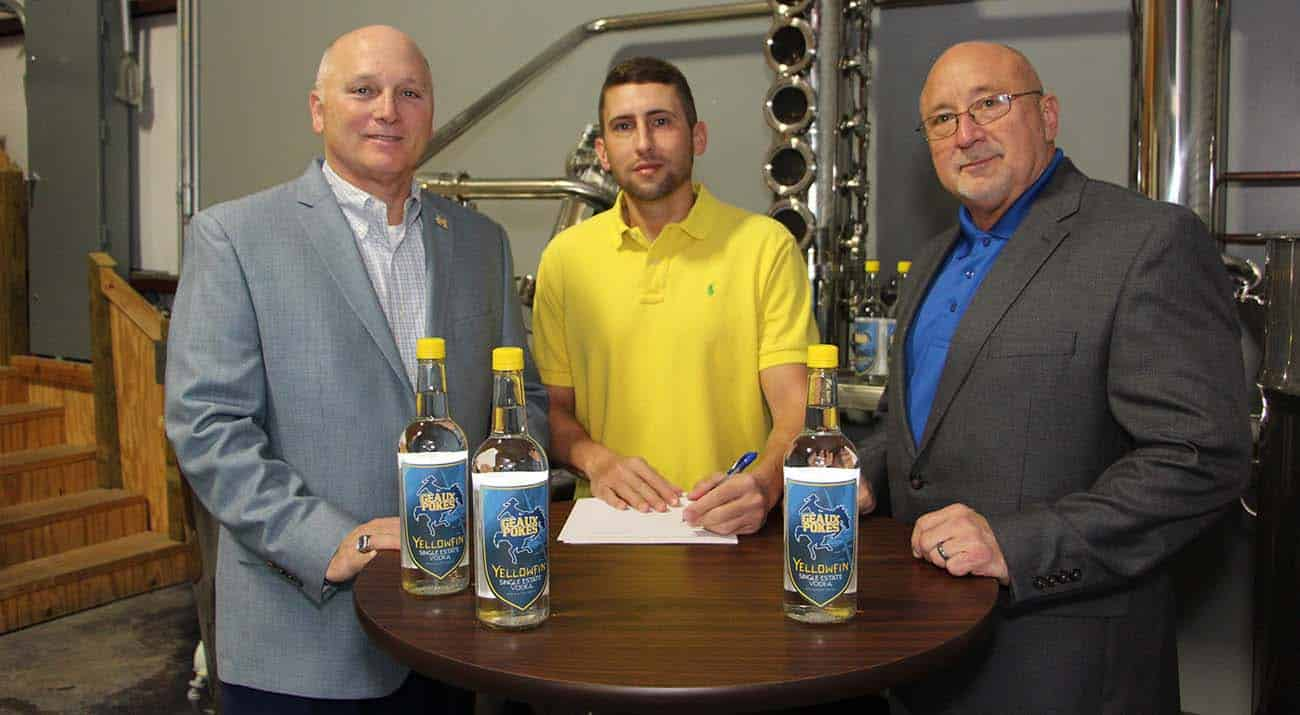 "McNeese State University has signed a marketing agreement with Yellowfin Distillery in Sulphur to receive a portion of the sale of a new beverage - Single Estate Vodka ""Geaux Pokes"" Edition – that is currently available in area retail stores. On hand for the signing are, from left, Dr. Daryl Burckel, McNeese president, Jamison Trouth, McNeese graduate and president and CEO of Yellowfin Distillery, and Dr. Mitchell Adrian, McNeese provost and vice president for academic affairs and enrollment management."