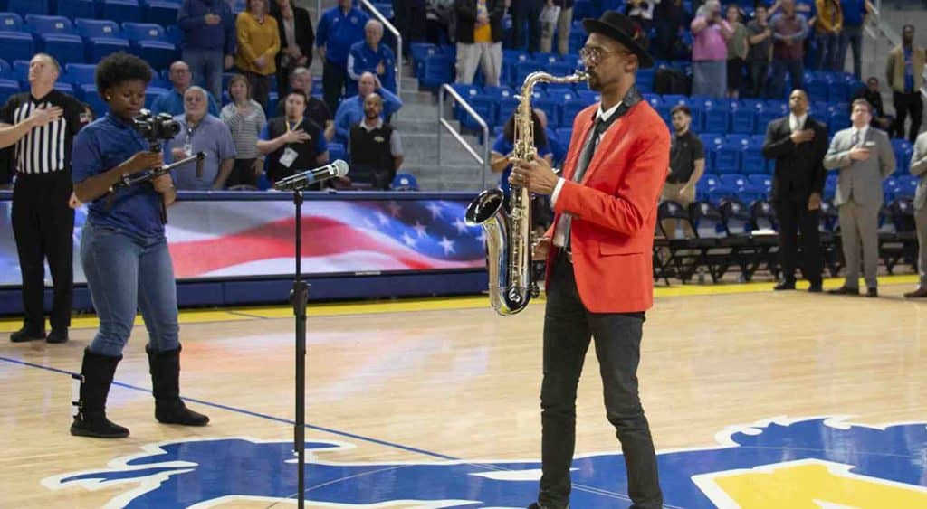 Mickey Smith plays the saxophone at a basketball game.
