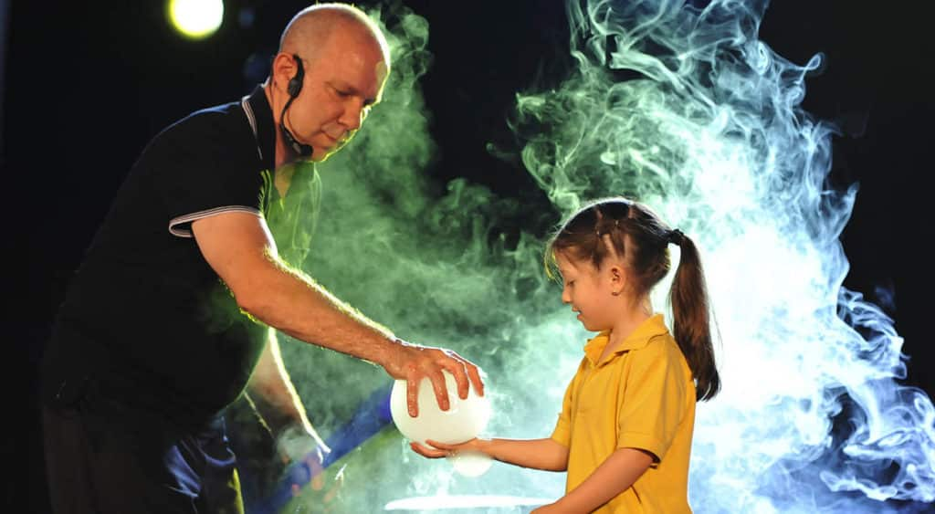 A member of the bubble bonanza fascinates a young girl with a large bubble
