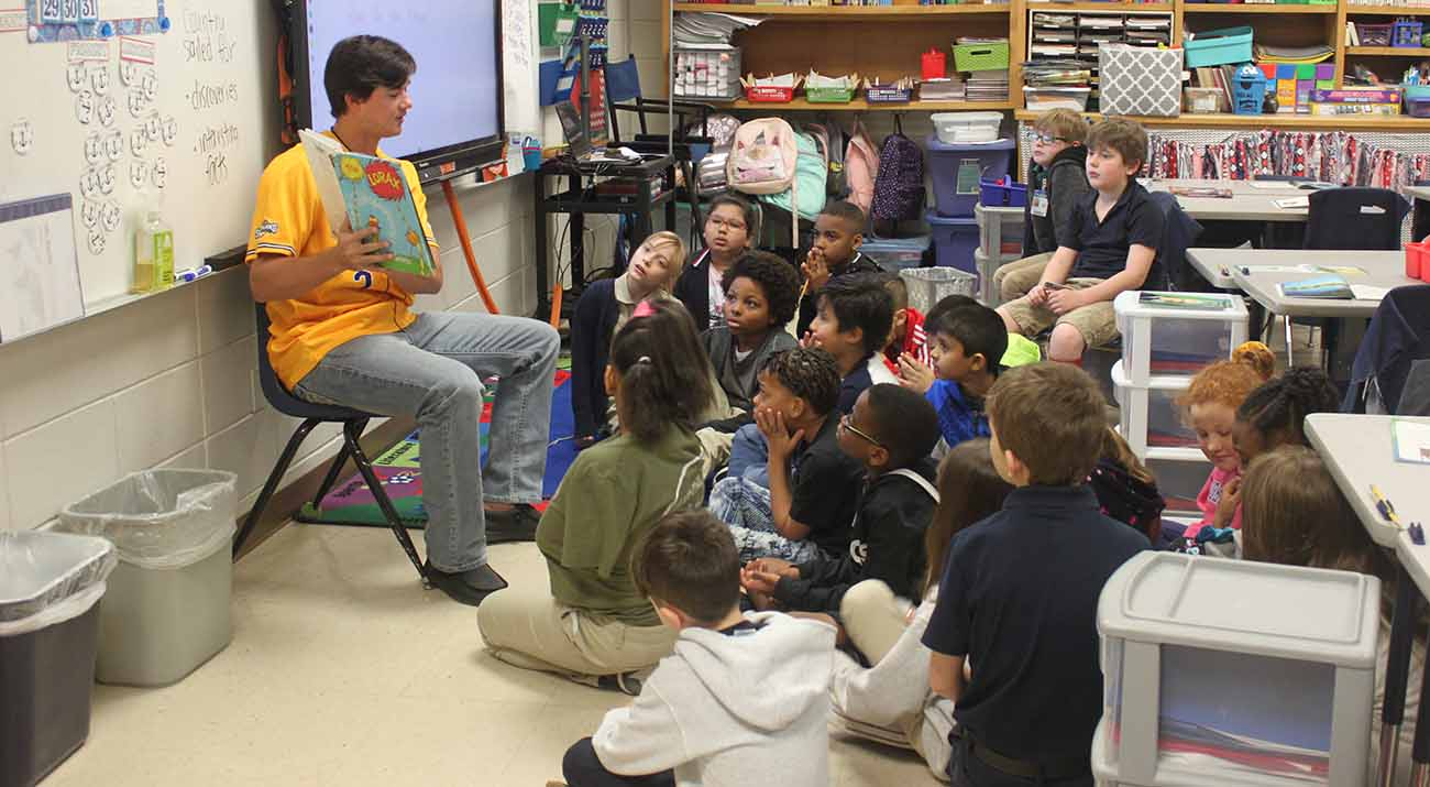McNeese student-athlete Welles Cooley reads to Nelson Elementary students.
