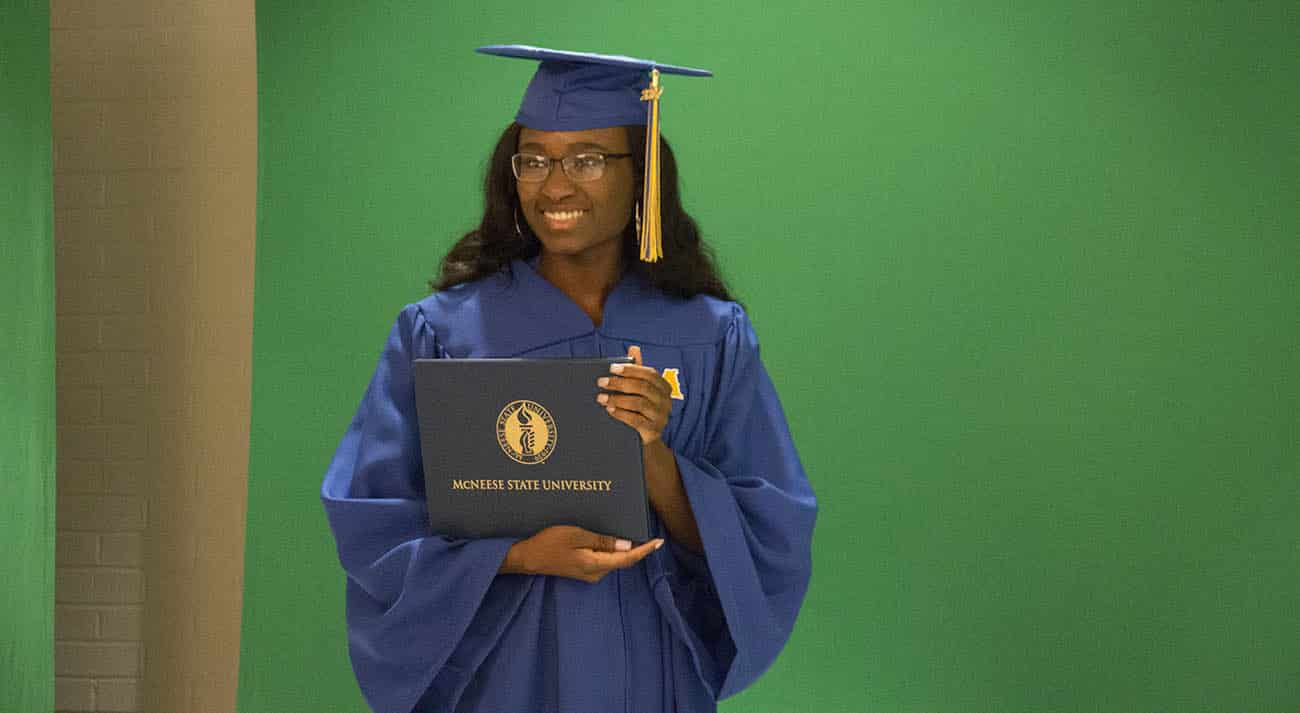 A female student stands with a diploma cover while getting her photo taken at GradFest.