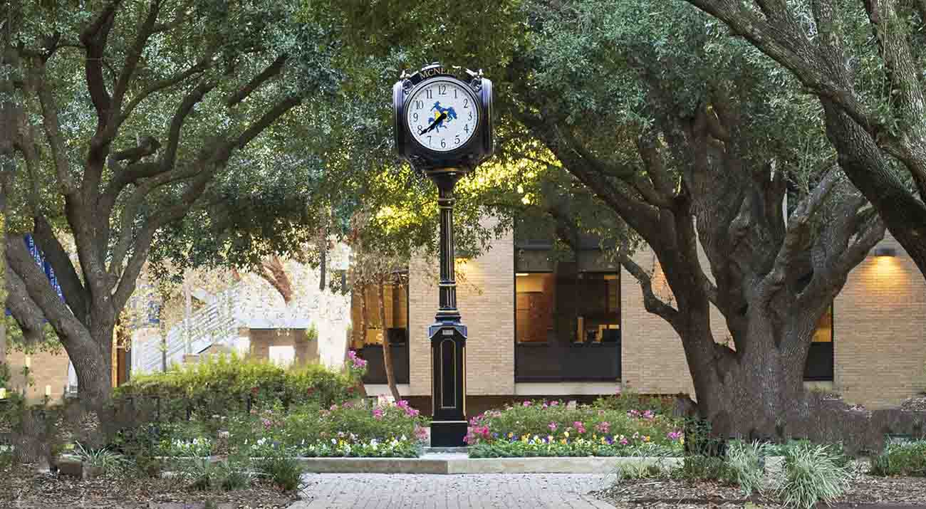 The four face clock in the Quad reads 7:39.