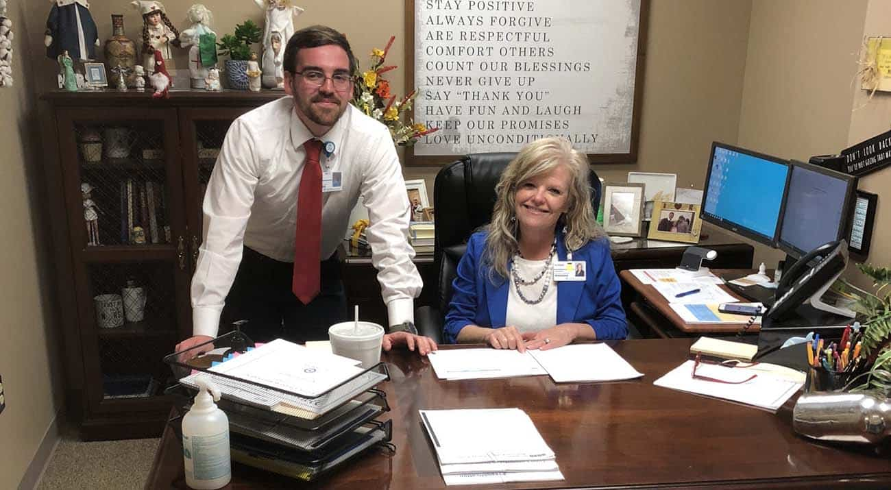 Tyler Culpepper and his internship leader smile for a photo in her office.