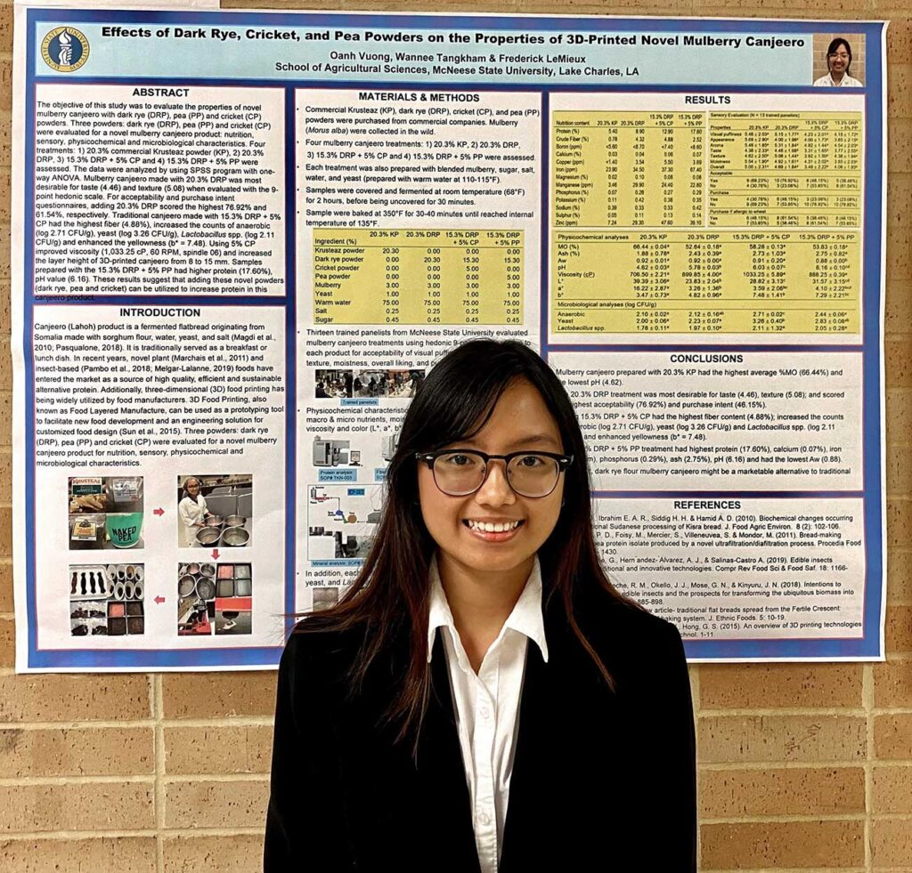 Oanh Vuong in front of poster