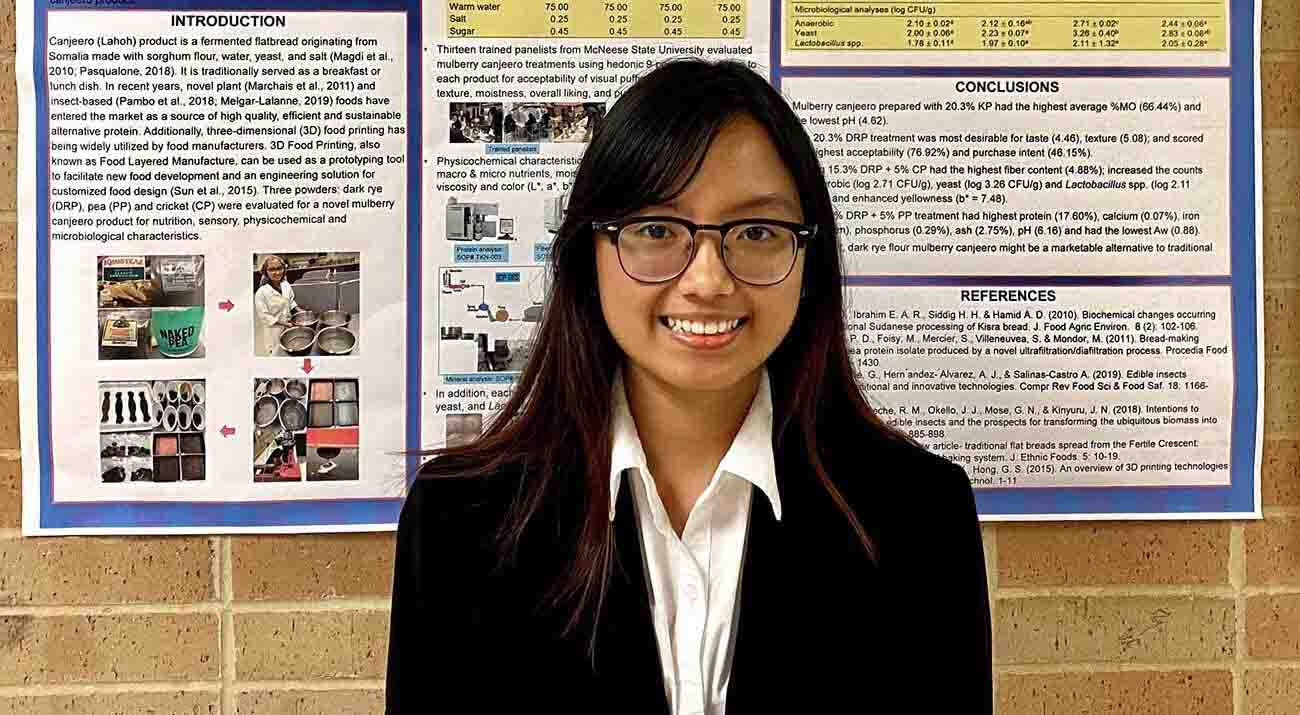 Oanh Vuong stands in front of her poster with graphs and photos the illustrate her research.