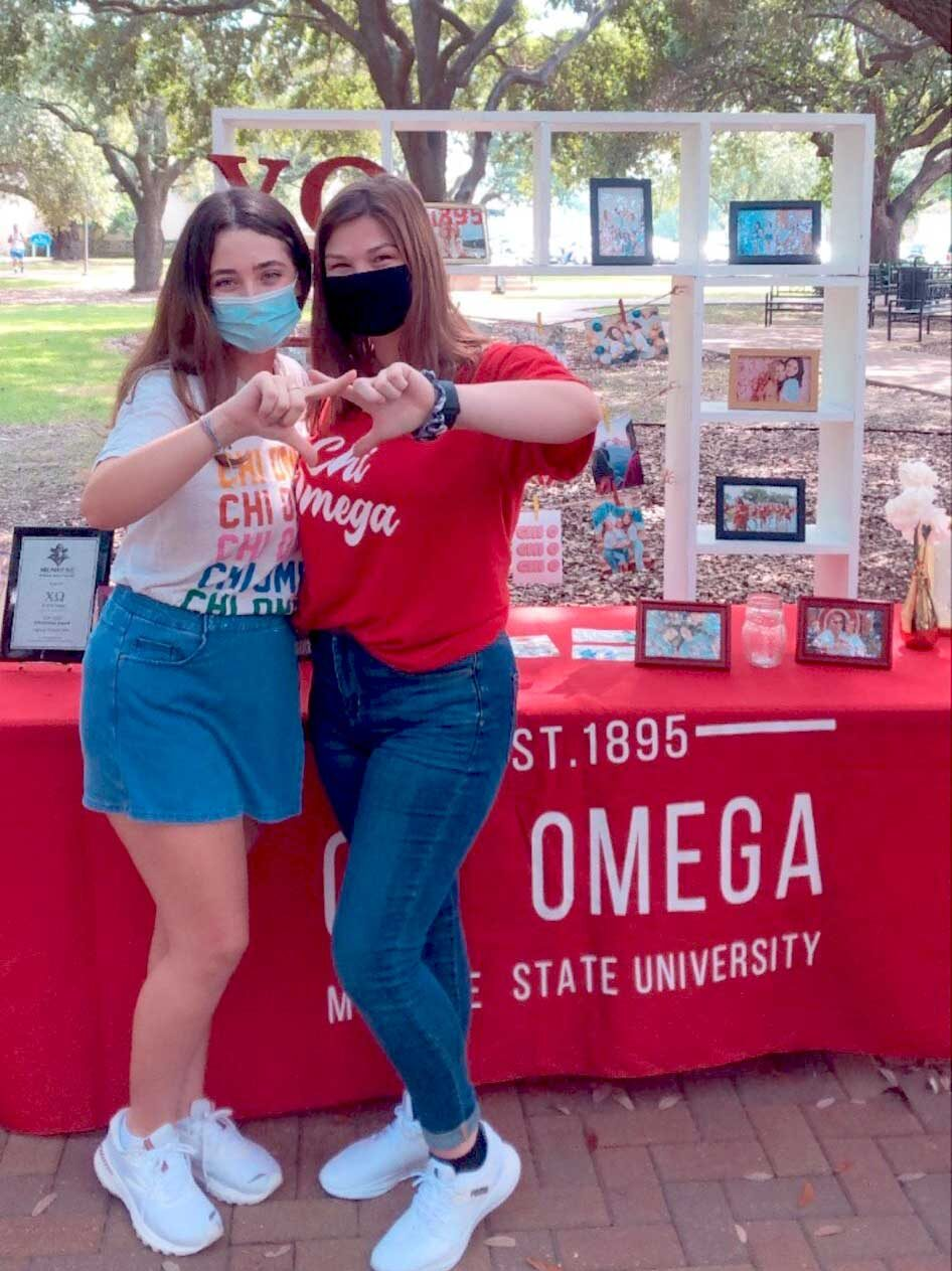 Students in front of Chi Omega poster