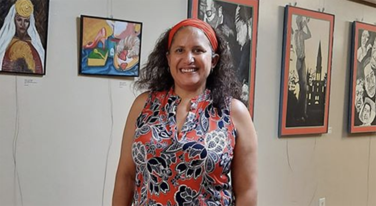 Lisa Wyatt stands in front of several pieces of her art.