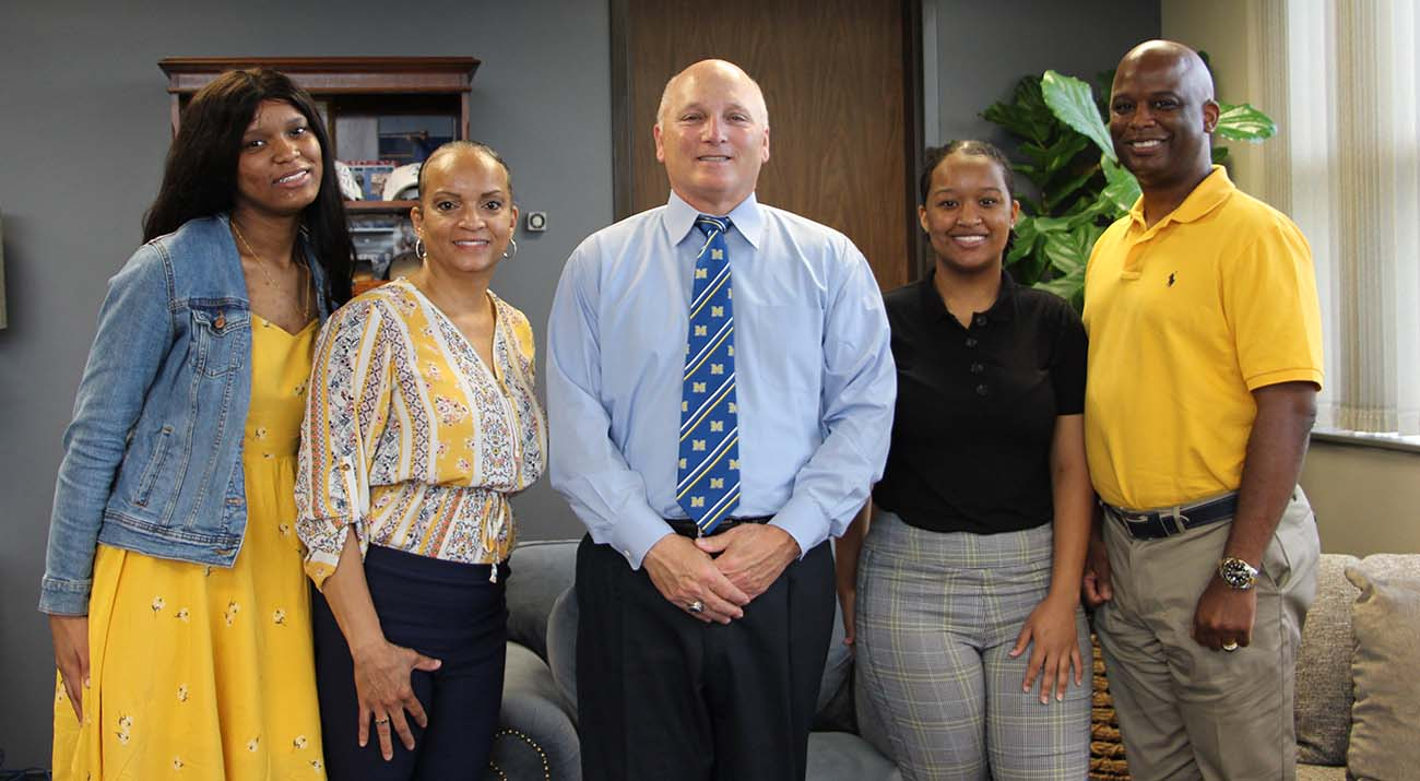 McNeese President Dr. Daryl Burckel stands with the Ned family in his office.