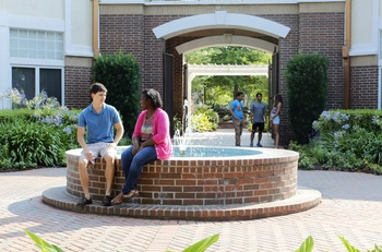 Students in housing quad by fountain