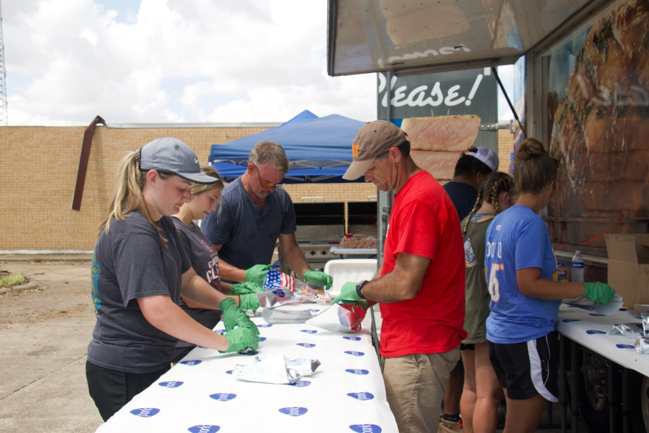 Dr. Chip LeMieux, alumni and agricutlural sciences students prepare sausage dogs