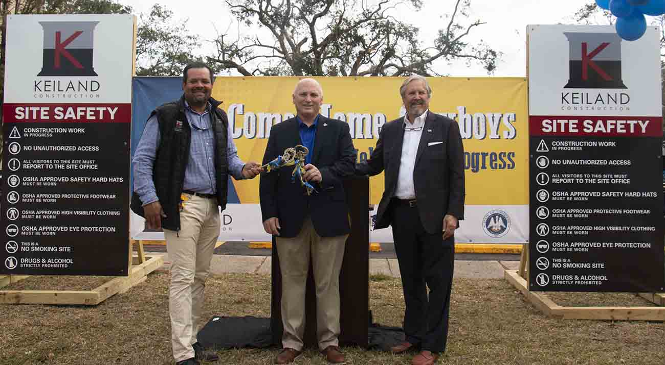 McNeese State University President Dr. Daryl Burckel, center, is presented with keys by Keith DuRousseau, Keiland Contruction president, left, and Buddy Ragland Jr., Coleman Partners Architects LLC owner, as a symbolic celebration of Frasch Hall, Frasch Hall Annex and the Frazar Memorial Library being released back to the university by Keiland Construction.