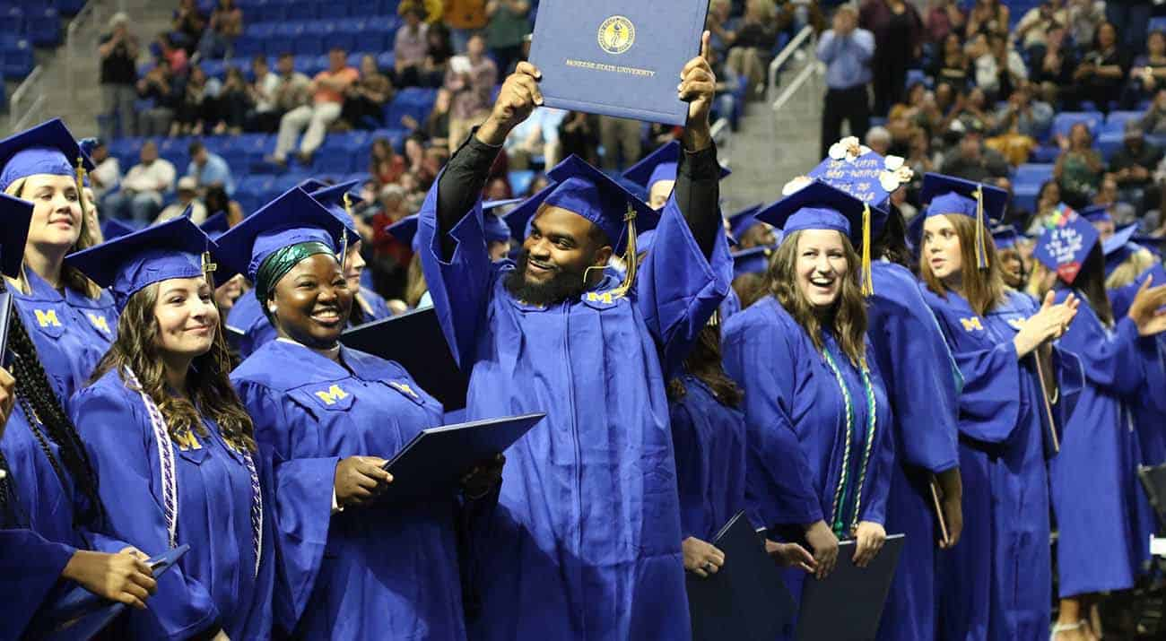 A McNeese graduate holds his diploma cover high as his peers look on.
