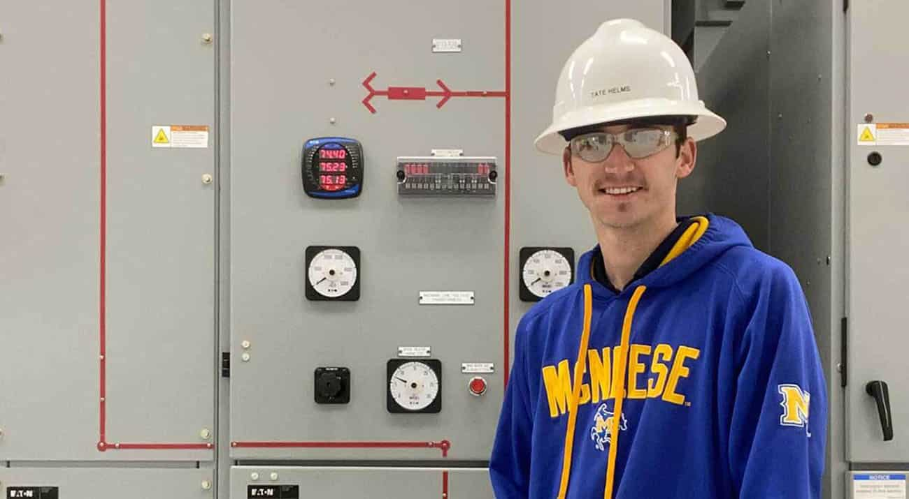 Tate Helms stands in front of machinery in a McNeese sweatshirt