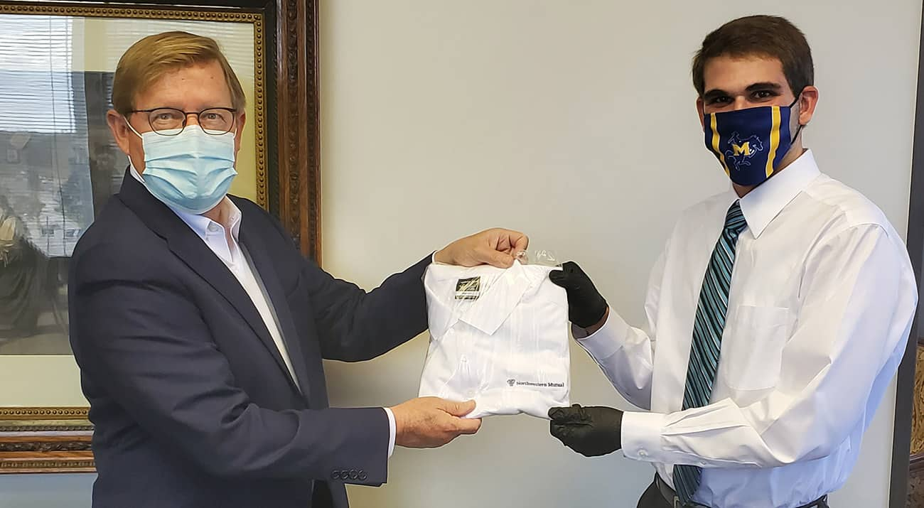 Zeb Bellimen, right, completed his internship with Northwestern Mutual and now works full time at the firm. Ted Harless, Northwestern Mutual Managing Director, left, presents Zeb a company shirt to welcome him to the team.