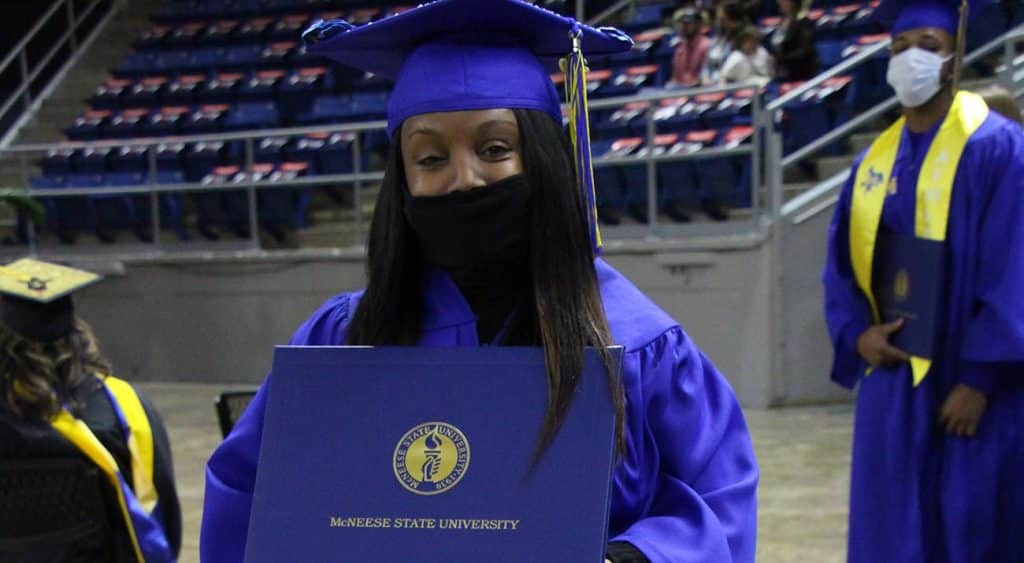 A young lady stands with her diploma cover.