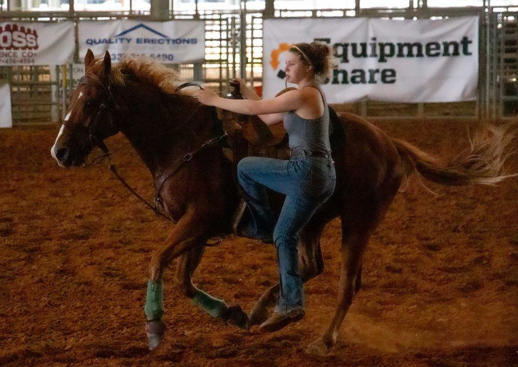 McNeese cowgirl dismounts horse during practice